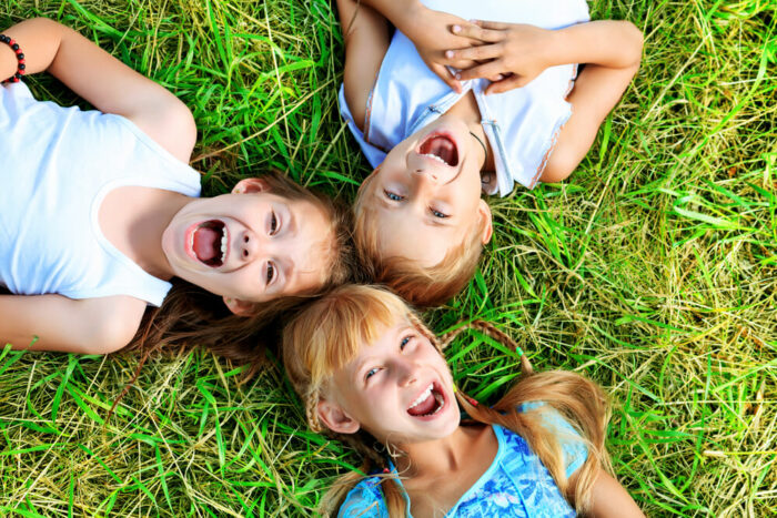 Three cute kids on the grass and laughing