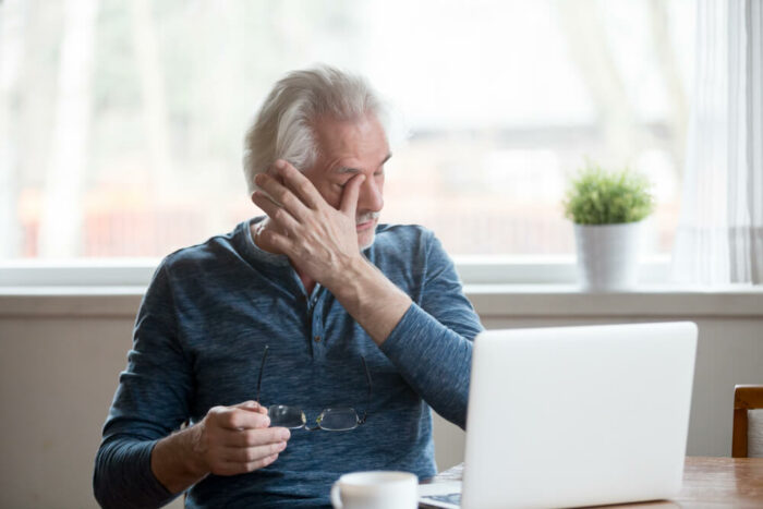 Older man rubbing his eye after taking off his glasses