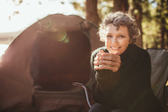 Mature woman, camping, holding a cup of tea