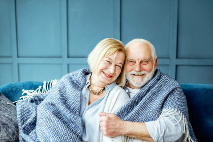 Mature couple wrapped up in a blue blanket in blue room