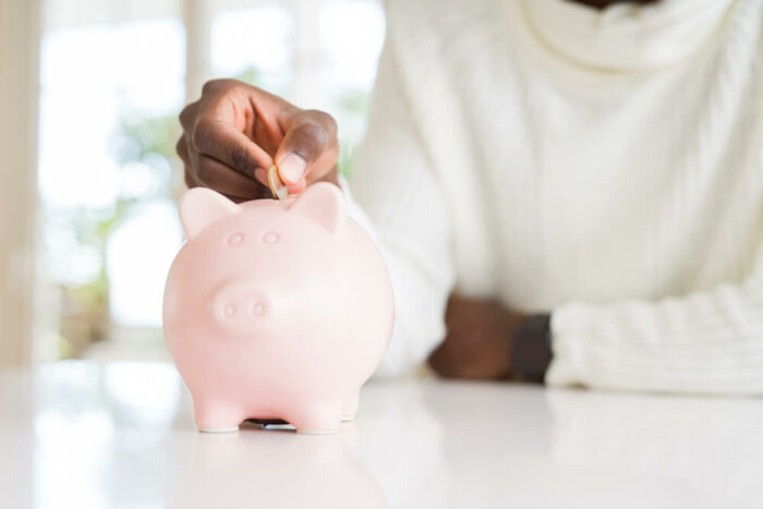 woman putting a coin in a pink piggy bank