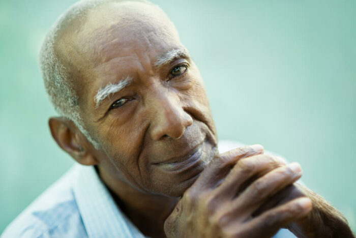 Older man looking at camera with small smile